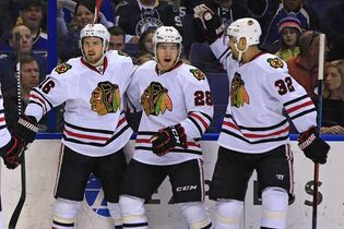 Chicago Blackhawks' Marcus Kruger, left, is congratulated by teammates Ben Smith, center, and Michal Rozsival, right, of the Czech Republic, after scoring a goal during the first period of an NHL hockey game against the St. Louis Blues, Sunday, Feb. 8, 2015, in St. Louis. The San Jose Sharks have traded forward Andrew Desjardins to the Chicago Blackhawks for Smith in a swap of fourth-line players. THE CANADIAN PRESS/AP/Billy Hurst