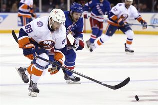 New York Islanders left wing Cory Conacher (89) and New York Rangers right wing Lee Stempniak (12) chase the puck during the first period of an NHL hockey game at Madison Square Garden, Tuesday, Oct. 14, 2014, in New York. The Vancouver Canucks have acquired Conacher from the New York Islanders in exchange for forward Dustin Jeffrey. THE CANADIAN PRESS/AP/John Minchillo