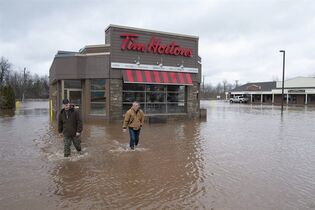Keegan Worden, left, and David Clement check on a flooded Tim Horton's location along Main Street in Sussex, N.B., on April 16, 2014. THE CANADIAN PRESS/David Smith