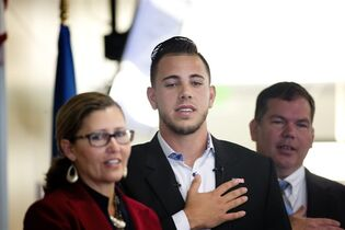 Miami Marlins pitcher Jose Fernandez, center, and immigration officials recite the