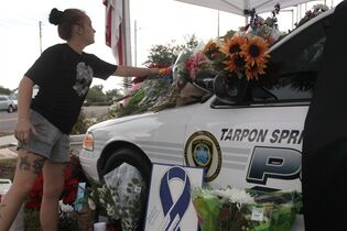 Cynthia Martinez, 23 of Tarpon Springs, leaves flowers at a memorial for a slain Tarpon Springs police officer in Tarpon Springs, Fla. on Sunday, Dec. 21, 2014. The Tarpon Springs Police Department identified the fallen officer as 45-year-old Charles Kondek, a 17-year veteran of the local police department. Originally from New York, Kondek had previously served on the New York City Police Department for more than five years, authorities said. (AP Photo/Tampa Bay Times, Monica Herndon)