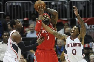 Houston Rockets forward Josh Smith (5) is defended by Atlanta Hawks guard Jeff Teague (0) and forward Paul Millsap during the first half of an NBA basketball game Tuesday, March 3, 2015, in Atlanta. (AP Photo/John Amis)