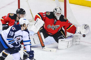 Calgary Flames' goalie Karri Ramo guards his net as Winnipeg Jets' centre Jim Slater tries to score during the first period of Friday's game at Scotiabank Saddledome.