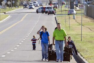 Scott Gatzulis and family, returning to Wichita from a Hawaii vacation, walk to their car at Mid-Continent Airport in Wichita, Kan., Thursday. Oct. 30, 2014, after a small plane crashed into the building killing several people including the pilot. Gatzulis said no traffic was allowed near the airport terminal, including shuttle buses. (AP Photo/The Wichita Eagle, Mike Hutmacher)