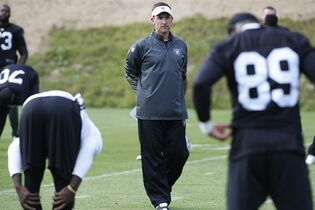 Oakland Raiders head coach Dennis Allen, canter, watches his players during a training session at Pennyhill Park, Bagshot, England, Thursday, Sept. 25, 2014. The Raiders will play the Miami Dolphins in an NFL football game at London's Wembley Stadium on Sunday Sept. 28. (AP Photo/Lefteris Pitarakis)