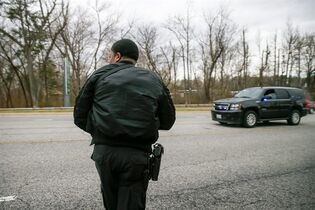 A police officer stands outside an entrance to Fort Meade directing traffic after a vehicle rammed a gate to the National Security Agency, Monday, March 30, 2015 in Fort Meade, Md. One person was killed in a firefight that erupted Monday after a car with two people tried to ram a gate at the Fort Meade, Md., military base near a gate to the National Security Agency, according to preliminary reports cited by two U.S. officials. (AP Photo/Andrew Harnik)