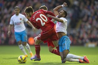 Liverpool's Adam Lallana, centre left, fights for the ball against Hull's Ahmed Elmohamady during their English Premier League soccer match at Anfield Stadium, Liverpool, England, Saturday Oct. 25, 2014. (AP Photo/Jon Super)