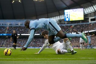 Manchester City's Yaya Toure, top, fights for the ball against Swansea's Ki Sung-Yeung during the English Premier League soccer match between Manchester City and Swansea at the Etihad Stadium, Manchester, England, Saturday Nov. 22, 2014. (AP Photo/Jon Super)