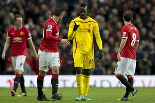 Liverpool's Mario Balotelli, centre gestures to Manchester United's Robin van Persie during the English Premier League soccer match between Manchester United and Liverpool at Old Trafford Stadium, Manchester, England, Sunday Dec. 14, 2014. (AP Photo/Jon Super)