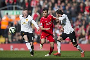 Liverpool's Philippe Coutinho, centre, is run off the ball by Manchester United's Wayne Rooney, left, and Juan Mata during the English Premier League soccer match between Liverpool and Manchester United at Anfield Stadium, Liverpool, England, Sunday, March 22, 2015. (AP Photo/Jon Super)