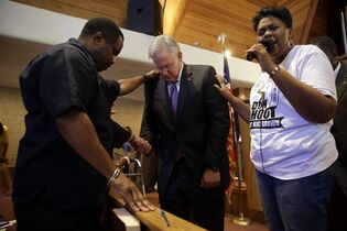 Missouri Gov. Jay Nixon, center, prays during a meeting of clergy and community members held to discuss law enforcement's response to demonstrations over the killing of Michael Brown, Thursday, Aug. 14, 2014, in Florissant, Mo. Nixon says