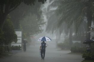 A Williams team crew member walks at the paddock as the rain suspends the qualifying session for the Malaysian Formula One Grand Prix at Sepang International Circuit in Sepang, Malaysia, Saturday, March 28, 2015. (AP Photo/Vincent Thian)