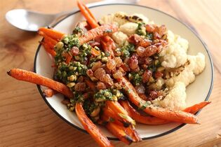 This April 6, 2015 photo shows roasted carrots with port raisins and spicy peanut herb sauce in Concord, N.H. The sauce can be prepped up to a day in advance, but don't add the peanuts until just before serving. (AP Photo/Matthew Mead)