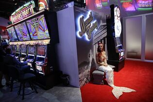 Samantha Whittemore sits on a bench in a mermaid costume at the Aruze boot during the Global Gaming Expo Tuesday, Sept. 30, 2014, in Las Vegas. U.S. casinos and the makers of the games found inside had a $240 billion economic impact and employed 1.7 million people in 2013, a study shows. The American Gaming Association was expected to announce the results of the study Tuesday. (AP Photo/John Locher)