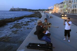 FILE - In this July 8, 2013 photo, musicians play trombones as a tourist from Colombia takes their picture along the Malecon in Havana, Cuba. President Barack Obama's announcement Wednesday, Dec. 17, 2014, of plans to re-establish diplomatic ties with the Caribbean nation gives hope to airlines, hotel chains and cruise companies _ all which have been quietly eyeing a removal of the travel ban _ that they soon will be able to bring tourists to Cuba. (AP Photo/Franklin Reyes, File)