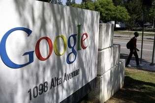 FILE - In this June 5, 2014 file photo, a man walks past a Google sign at the company's headquarters in Mountain View, Calif. Google reports quarterly financial results after the market closes Thursday, Oct. 16, 2014. (AP Photo/Marcio Jose Sanchez, File)