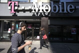 FILE - In this Sept. 12, 2012 file photo, a man uses a cellphone as he passes a T-Mobile store in New York. T-Mobile on Tuesday, Dec. 16, 2014 announced it is now letting customers carry over their unused cellular-data allotments for up to a year. (AP Photo/Mark Lennihan, File)