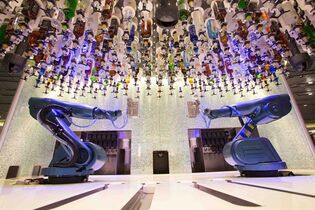 "This undated photo shows the ""bionic bar"" aboard Royal Caribbean's Quantum of the Seas cruise ship. The bar features two robotic arms that can craft, mix and pour a variety of cocktails and drinks. The bionic bar is one of a number of first-at-sea attractions on the ship, which also offers bumper cars, simulated skydiving and an observation capsule with a bird's eye view 300 feet (91 meters) above the water. (AP Photo/Royal Caribbean, File)"