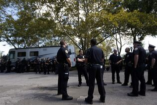 Police officers gather near the entrance of the Electric Zoo music festival venue on New York's Randall's Island, Friday, Aug. 29, 2014. Heightened security has been placed at the festival, after the final day of last year's festival was called off. Two people died from an overdose of MDMA combined with hyperthermia at the festival last year. (AP Photo/Jason DeCrow)