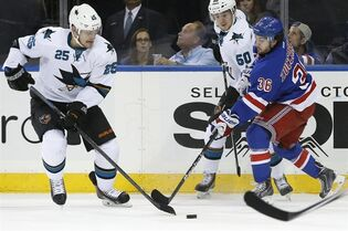 San Jose Sharks left wing Tye McGinn (25) and center Chris Tierney (50) go after a loose puck with New York Rangers right wing Mats Zuccarello (36), of Norway, defending during the first period of an NHL hockey game at Madison Square Garden in New York, Sunday, Oct. 19, 2014. (AP Photo/Kathy Willens)