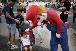 "A person dressed as Mario pats a child on the head in Times Square on Monday, July 28, 2014 in New York. New York City Mayor Bill de Blasio said Monday that he believes the people wearing character costumes in Times Square should be licensed and regulated. Dozens of people dressed as kids' favorites like Elmo, Cookie Monster and Batman stand near 42nd Street and pose for photos with tourists in exchange for money. De Blasio said the practice has ""gone too far."" A man dressed as Spider-man was arrested Saturday, July 28, 2014, after punching a police officer who told him to stop harassing tourists. The City Council is working on legislation that would require the characters to get a city-approved license. (AP Photo/Seth Wenig)"