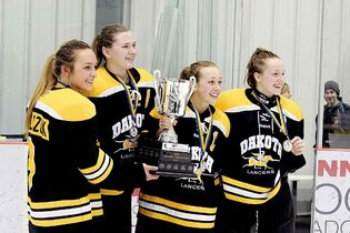 The Dakota Lancers defeated the Fort Richmond Centurions 2-0 in the WWHSHL Division A Championships on March 13, 2014. In this file photo, several Lancers teammates celebrate with the championship trophy. From Left: Mackenzie Kowalczuk, Trina Allard, Madison Stratton and Ashten Vankoughnett.