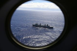 FILE - In this March 31, 2014 file photo, HMAS Success is viewed from a Royal New Zealand Air Force P3 Orion while both search for the missing Malaysia Airlines Flight 370 in the southern Indian Ocean, near the coast of Western Australia. Nearly a year has passed since Malaysia Airlines Flight 370 vanished on a flight from Kuala Lumpur to Beijing, sparking one of the most perplexing mysteries of modern times. Since then, search crews have taken to air, land and sea in a thus-far fruitless hunt for the plane and the 239 people who disappeared with it. (AP Photo/Rob Griffith, File)