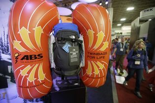 """People walks pass The North Face exhibit displaying its new avalanche airbag """"modulater system"""" that is a set of dual air bags that be attached to any backpack at the Outdoor Retailer Show Wednesday, Jan. 21, 2015, in Salt lake City. The theory is that skiers get used to their favorite packs and don't always want to use a new pack to have the air bag. (AP Photo/Rick Bowmer)"""