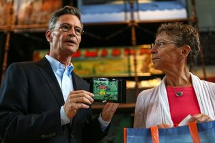 Museum of History and Industry Executive Director Leonard Garfield accepts the donation Tuesday July 22, 2014, in Seattle, of the first legal recreational marijuana purchase in Seattle from Deb Green, right, who made the purchase at Cannabis City on July 8, 2014. (AP Photo/seattlepi.com, Joshua Trujillo)