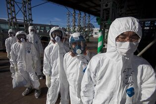 FILE - This Nov. 12, 2011, file photo, shows workers in protective suits and masks as they wait to enter the emergency operation center at the crippled Fukushima Dai-ichi nuclear power station in Okuma, Japan. A U.S. science advisory report says a key lesson from Japan's Fukushima nuclear accident is that the nation's nuclear industry needs to focus more on the highly unlikely but super-serious worst case scenarios and radiation traveling further than previously figured. (AP Photo/David Guttenfelder, File)
