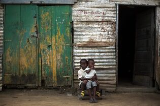Children sit in from of their home in the St. Paul Bridge neighborhood of Monrovia, Liberia, Sunday Sept. 28, 2014. Six months into the world's worst-ever Ebola outbreak, and the first to happen in an unprepared West Africa, the gap between what has been sent by other countries and private groups and what is desperately needed is huge. Even as countries try to marshal more resources to close the gap, those needs threaten to become much greater, and possibly even insurmountable. (AP Photo/Jerome Delay)