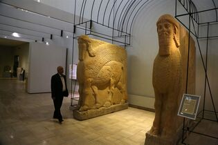 FILE - In this March 1, 2015. file photo, Aaman at Iraq's National Museum in Baghdad walks past two ancient Assyrian winged bull statues. Islamic State militants
