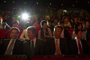 A spectator takes a photograph as Chinese and foreign film executives wait for a contract signing event to begin as part of the Beijing International Film Festival in Beijing, Monday, April 20, 2015. Chinese and foreign film producers, companies and investment firms signed movie cooperation deals worth 13.8 billion RMB ($2.3 billion) on Monday, demonstrating how foreign movie makers increasingly want a piece of the growing Chinese market. (AP Photo/Mark Schiefelbein)
