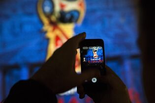 A man takes a photo of the official logo for the 2018 FIFA World Cup, as it is presented on the facade of the Bolshoi Theatre in Moscow, Russia, Wednesday, Oct. 29, 2014. FIFA President Sepp Blatter has revealed the logo for the 2018 World Cup in Russia - with the help of a crew of cosmonauts. The logo depicts the World Cup trophy in red and blue, colors from the Russian flag, with gold trim. (AP Photo/Pavel Golovkin)