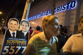 In this Sept.25, 2014 photo, a banner with the face of the Pentecostal pastor Silas Malafaia, right, and the political candidate Sostenes Cavalcante, is placed on the sidewalk in front of Assemblies of God church, in Rio de Janeiro, Brazil. Malafaia who supports fellow coreligionist and presidential challenger Marina Silva, is part of a rapidly swelling movement that is strongly rooted among poorer Brazilians, a group that otherwise heavily favors presidential Incumbent Dilma Rousseff's Workers Party, which has lifted millions from poverty with expansive social welfare programs and the creation of millions of new jobs. (AP Photo/Leo Correa)