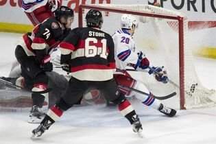 New York Rangers left wing Chris Kreider, right, scores on a bouncing puck under pressure from Ottawa Senators defenceman Mark Borowiecki, left, and right wing Mark Stone during first period NHL hockey action in Ottawa on Thursday, March 26, 2015. THE CANADIAN PRESS/Adrian Wyld