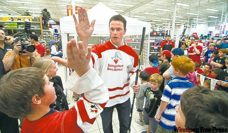 Chicago Blackhawks' Jonathan Toews high-fives young fans at Canadian Tire last week as he promotes the Jumpstart program for families who cannot afford to enrol their children in organized sports.