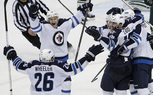 The Jets celebrate Andrew Ladd's game-winning overtime goal Saturday night in Minnesota.
