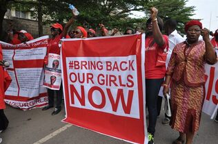 FILE - In this file photo taken Tuesday, Oct. 14, 2014, people demonstrate calling on the Nigerian government to rescue girls taken from a secondary school in Chibok region, in the city of Abuja, Nigeria . Days after Nigeria's military raised hopes by announcing Islamic extremists have agreed to a cease-fire, Boko Haram is still fighting and there is no word about 219 schoolgirls held hostage for six months. Officials had said talks with Nigeria's Islamic extremist rebels would resume in neighboring Chad this week, but there was no confirmation that negotiations had resumed by Wednesday. (AP Photo/Olamikan Gbemiga File)