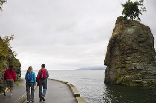 This undated image provided by Vancouver Tourism shows strollers on Vancouver's Stanley Park seawall in British Columbia, Canada, as they pass Siwash Rock while looking out onto English Bay. One of the world's largest urban parks, Stanley Park is named for the British lord for who gave his name the National Hockey's League's Stanley Cup. (AP Photo/Tourism Vancouver/ Canadian Tourism Commission)
