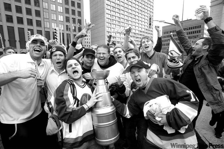 MIKE.DEAL@FREEPRESS.MB.CA Hockey fans celebrate at Portage and Main Tuesday after hearing announcement of the return of the NHL to Winnipeg.