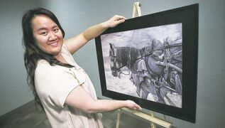 Janellyn Marcial displays a painting for auction at the May 30 Winnipeg Timeraiser.
