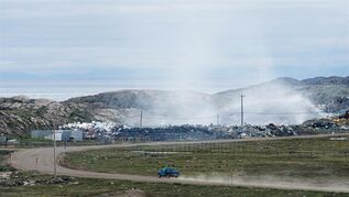 A car approaches the city dump as smoke rises from a fire burning among the garbage, Thursday, July 10, 2014 in Iqaluit, Nunavut. The long-smouldering dump fire in Iqaluit, dubbed the