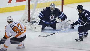 The Philadelphia Flyers' Jakub Voracek scores on Winnipeg Jets goaltender Ondrej Pavelec as Blake Wheeler defends during first period NHL action at the MTS Centre in Winnipeg on Sunday, Dec. 21, 2014.