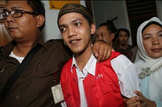 Child sexual abuse suspect Agun Iskandar, center, is escorted by security officers after his trial at South Jakarta District Court in Jakarta, Indonesia, Monday, Dec. 22, 2014. An Indonesian court has sentenced five janitors to up to eight years in prison over the rape of a kindergartner at prestigious school in Indonesia. (AP Photo/Tatan Syuflana)