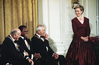 FILE - In this Dec. 5, 1993 file photo, first lady Hillary Rodham Clinton wears an Oscar de la Renta dress, right, as she laughs with conductor Georg Solti, from left, founder of the Dance Theatre of Harlem Arthur Mitchell, and entertainer Johnny Carson during a ceremony in the East Room of the White House in Washington for the Kennedy Center Honors. The designer, who died Monday, Oct. 20, 2014, at 82, shaped American couture half a century ago when it emerged as a serious rival to European fashion designers (AP Photo/Wilfredo Lee, File)