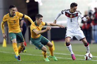 Austarlia's Jason Davidson, left, and Matthew McKay, center, challenge for the ball with Germany's Mesut Ozil, right, during a soccer friendly match between Germany and Australia in Kaiserslautern, Germany, Wednesday, March 25, 2015. (AP Photo/Michael Probst)