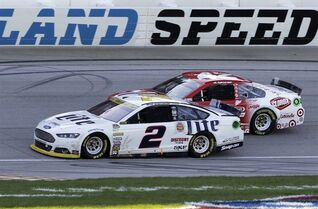 Brad Keselowski (2) drives past Kyle Larson (42) during the NASCAR Sprint Cup series auto race at Chicagoland Speedway in Joliet, Ill., Sunday, Sept. 14, 2014. Keselowski won the race. (AP Photo/Nam Y. Huh)
