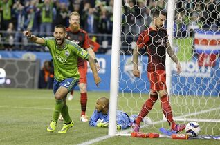 Seattle Sounders' Clint Dempsey, left, celebrates after he scored a goal on Portland Timbers goalkeeper Adam Kwarasey, second from right, as Timbers' Alvas Powell, right, stands in the goal in the second half of an MLS soccer match, Sunday, April 26, 2015, in Seattle. The Sounders beat the Timbers 1-0. (AP Photo/Ted S. Warren)