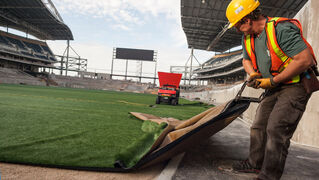 A worker tugs on one of the final piece of artificial turf at Investors Group Field. The new turf was laid down this week by the company FieldTurf and they will add 500 tonnes of rubber and sand to create the
